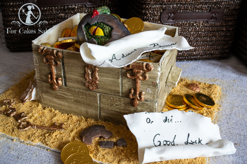 Dungeons and Dragons Crate Cake. It has a baby dragon hatching from an egg, a broken scroll and plenty of gold coins.