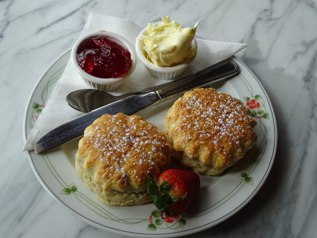 two buttermilk scones served with clotted cream , jam and a strawberry.